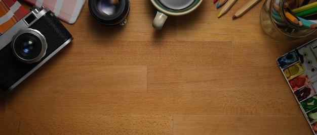 カメラ、ペイントツール、消耗品、コピースペースの木製テーブルの上から見る