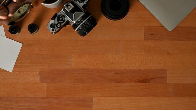 Вид сверху деревянного стола с камерой, расходными материалами и копией пространства в комнате домашнего офиса