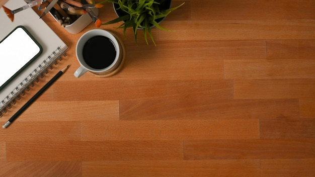 コピースペース、コーヒーカップ、文房具、植木鉢と木製テーブルの上面図