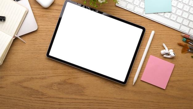 Вид сверху деревянного стола с цифровым планшетом, включая аксессуары для обтравочного контура и канцелярские принадлежности