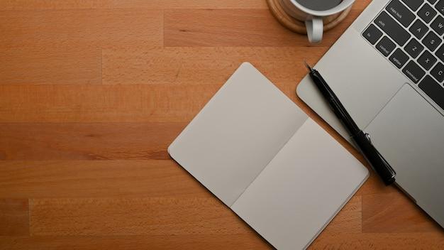 開いた空白のノートブックラップトップとコピースペースと木製のテーブルの上面図