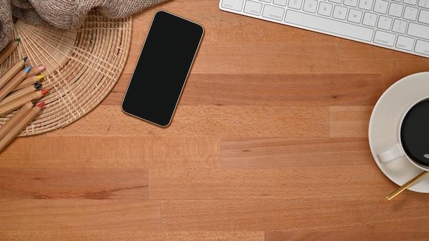 スマートフォン、コーヒーカップ、キーボード、鉛筆、コピースペースと木製のテーブルの上面図