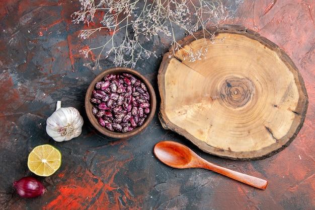 Вид сверху на деревянный поднос, фасоль, чеснок, лук, лимон и ложку на фоне смешанного цвета