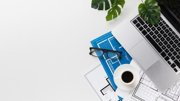 Вид сверху рабочего стола с чертежами и ноутбуком