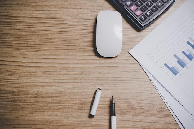 Вид сверху рабочего стола с ручкой, ноутбуком, планшетом, мышью, калькулятором и графикой.