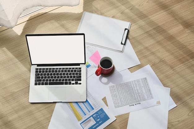木の床に空白の画面のラップトップ、ドキュメント、コーヒーカップと職場の上面図。