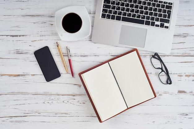 作業スペースの上面図:オフィスのテーブルにあるメモ帳、ラップトップ、電話、ペン、メガネ。無人