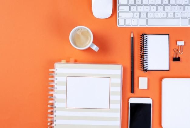 Вид сверху на рабочее место, оранжевый письменный стол с клавиатурой, карандашом, мобильным телефоном, мышью, ноутбуком и чашкой кофе и дневником. с копией пространства.