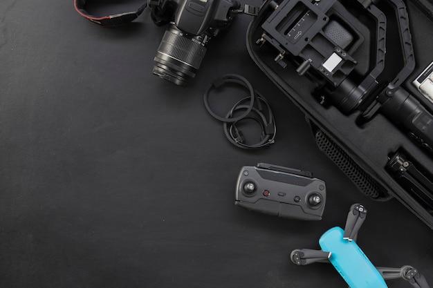 Вид сверху рабочего места фотографа с цифровой камерой и аксессуарами на черном фоне Premium Фотографии