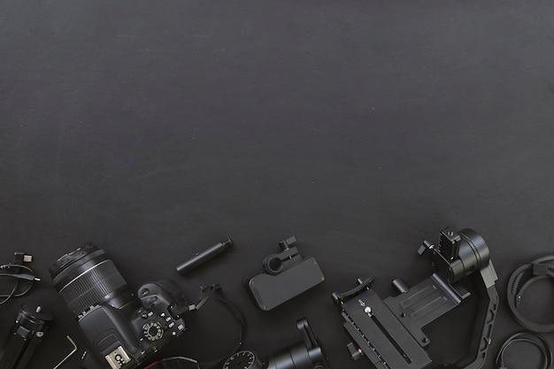 Вид сверху рабочего места фотографа с цифровой камерой и аксессуарами на черном фоне