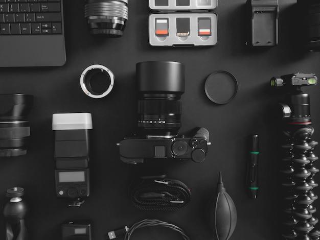 黒いテーブル背景にデジタルカメラ、フラッシュ、クリーニングキット、メモリカード、三脚、カメラアクセサリーと作業スペースカメラマンのトップビュー