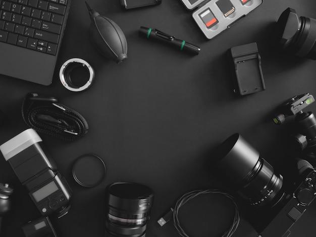 Вид сверху фотографа рабочего пространства с цифровой камерой, вспышкой, набором для чистки, картой памяти, штативом и камерой для аксессуаров на черном фоне стола