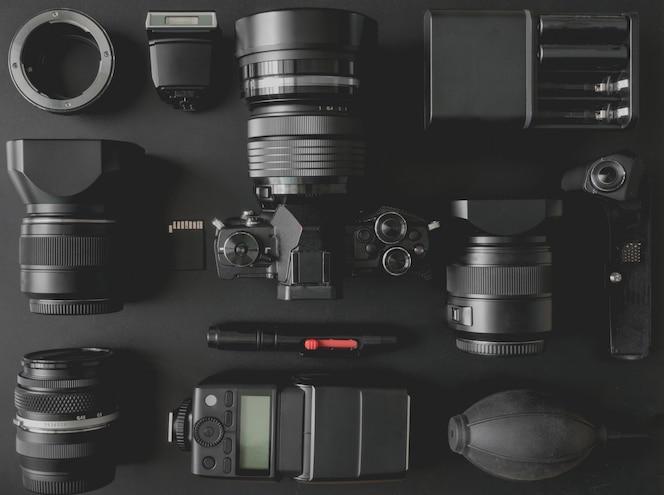 블랙 테이블 배경에 미러리스 카메라 시스템, 카메라 플래시, 배터리 충전기, 카메라 클리닝 키트, 메모리 카드 및 카메라 액세서리가 장착 된 작업 공간 사진 작가의 상위 뷰
