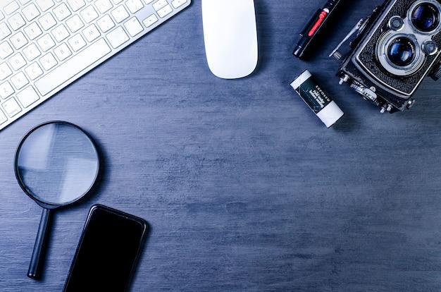 Взгляд сверху фотографа места работы с винтажной камерой, черни, компьютерной клавиатурой, мышью и увеличительным стеклом на деревянном фоне.
