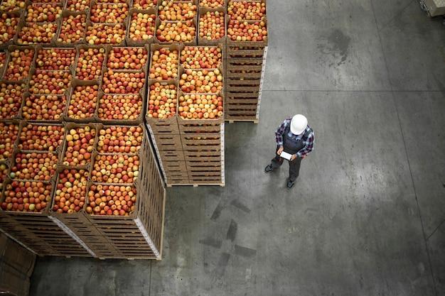 유기농 식품 공장 창고에서 사과 과일 상자에 의해 서 작업자의 상위 뷰.