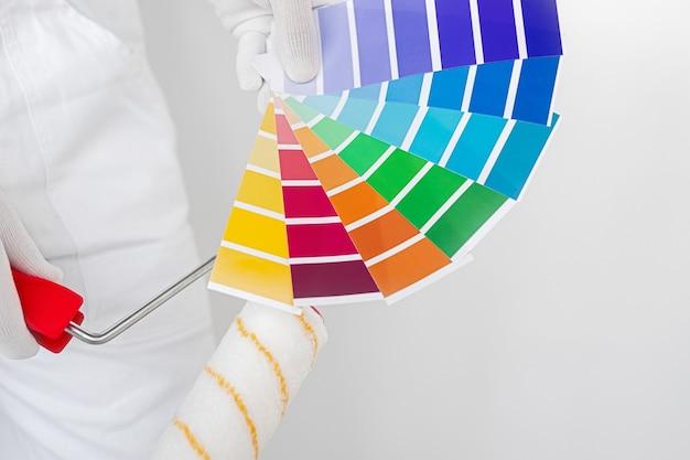 Вид сверху рабочего с малярным валиком и красочной палитрой