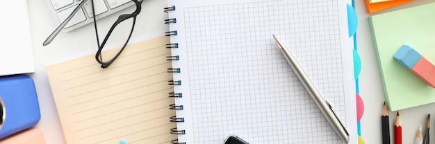 職場の平面図。ノートブックを開くと銀のペン。黒いメガネ。デスクトップ上の白いモダンなキーボード。仕事の詳細。オフィス文具と創造性の概念