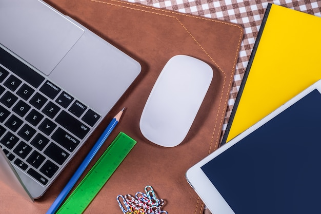 ノートブック、鉛筆のスマートフォン、黄色のテキストブックを開いて作業テーブルのトップビュー