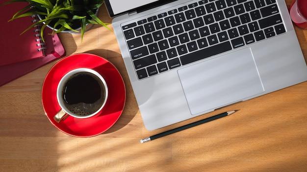 木製のテーブル背景にラップトップコンピューター、コーヒーカップ、オフィスアクセサリー付きの作業テーブルのトップビュー