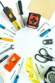 Вид сверху рабочих инструментов, гаечный ключ, отвертка, уровень, рулетка, болты и защитные очки на белом фоне.