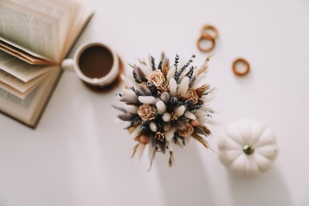 Вид сверху рабочего места или офисного стола с чашкой кофе, книгой и цветами на белом фоне