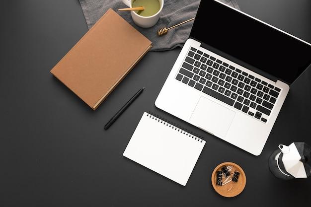 Вид сверху рабочей области с повесткой дня и ноутбуком