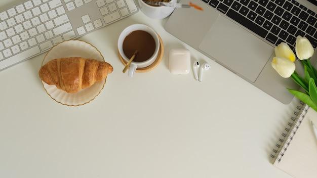 朝食の食事、ラップトップ、イヤホン、コピースペースのあるワークスペースの上面図