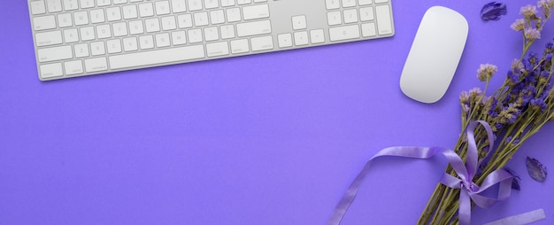 Вид сверху рабочей области с компьютерной клавиатурой, цветами и копией пространства на фиолетовом столе