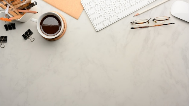 홈 오피스 룸에서 컴퓨터 키보드, 소모품, 커피 컵 및 복사 공간이있는 작업 공간의 상위 뷰