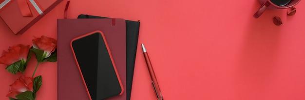 Вид сверху рабочей области с копией пространства, смартфон, дневник тетради, канцтовары и розы на розовом фоне стола
