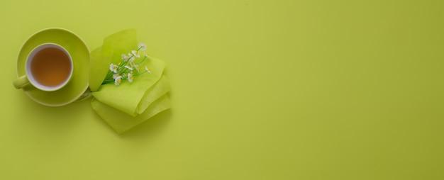 Вид сверху рабочей области с копией пространства, чашка чая и украшения на зеленом столе