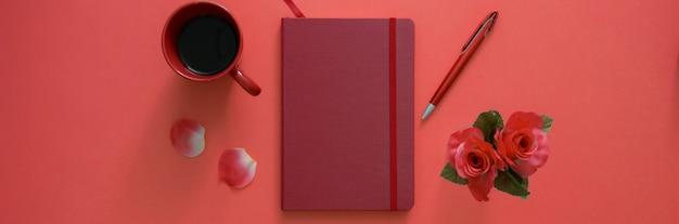 Вид сверху рабочей области с блокнотом дневника, ручкой, кофейной чашкой и вазой розы на розовом столе