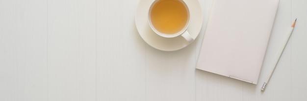 Вид сверху рабочей области с блокнотом дневника, карандашом, чашкой чая и местом для копирования на доске