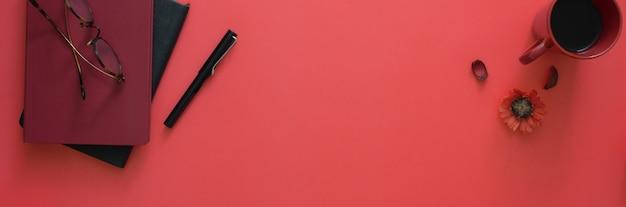 Вид сверху рабочей области с дневниками, очками, кофейной чашкой и копией пространства на розовом столе