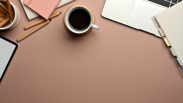 Вид сверху на рабочее пространство с цифровыми устройствами, канцелярскими принадлежностями, чашкой кофе и копией пространства на розовом столе