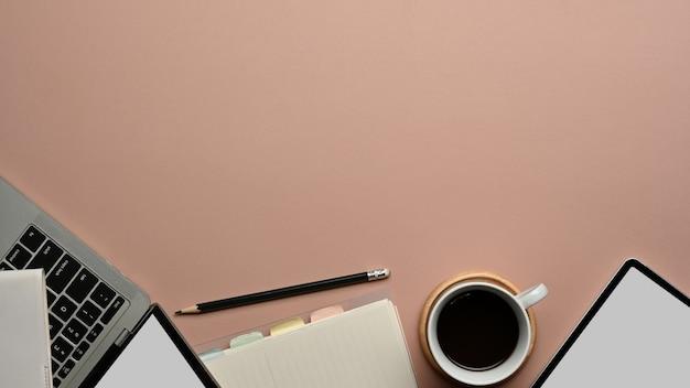 デジタルデバイス、文房具、コーヒーカップ、ピンクのテーブルのコピースペースとワークスペースの上面図
