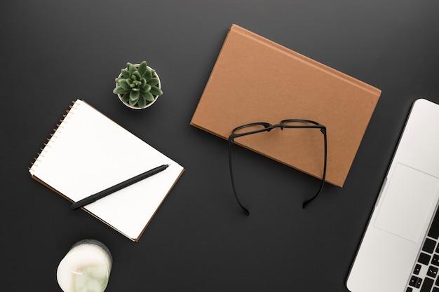 Вид сверху рабочей области с очками и ноутбуком