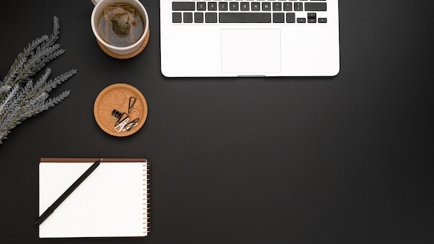 Вид сверху рабочей области с ноутбуком и чашкой чая
