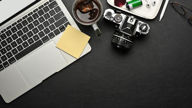 ラップトップ、カメラ、消耗品、黒い机の上のコピースペースとワークスペースの上面図