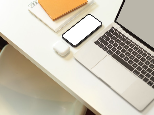 ラップトップスマートフォンとホームオフィスルームの白い椅子と白い机の上の文房具とワークスペースの上面図
