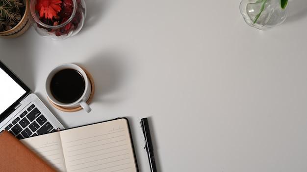 노트북, 편지지, 커피 컵 및 흰색 테이블에 복사 공간이있는 작업 공간의 상위 뷰