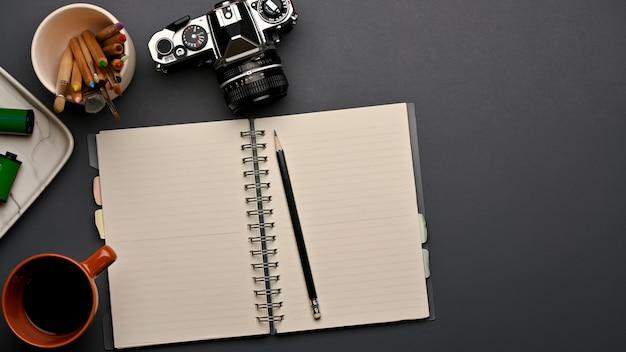 開いた空白のノートブック、カメラ、ホームオフィスルームの備品とワークスペースの上面図
