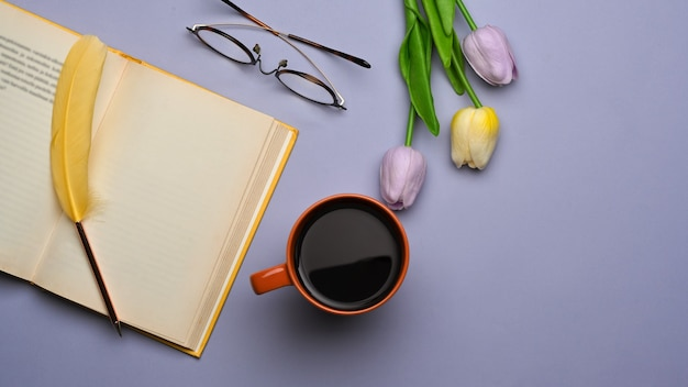 보라색 테이블에 열린 책, 커피 업, 안경 및 튤립 꽃이있는 작업 공간의 상위 뷰