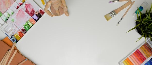 흰색 테이블에 페인트 도구, 노트북, 장식 및 복사 공간이있는 작업 공간의 상위 뷰