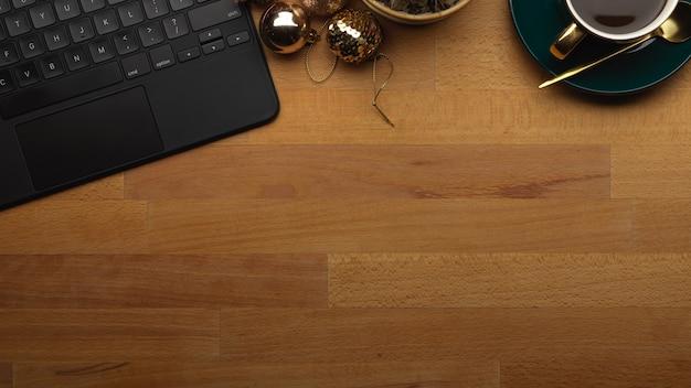 Вид сверху рабочей области с чашкой кофе с клавиатурой планшета и копией пространства на деревянном столе