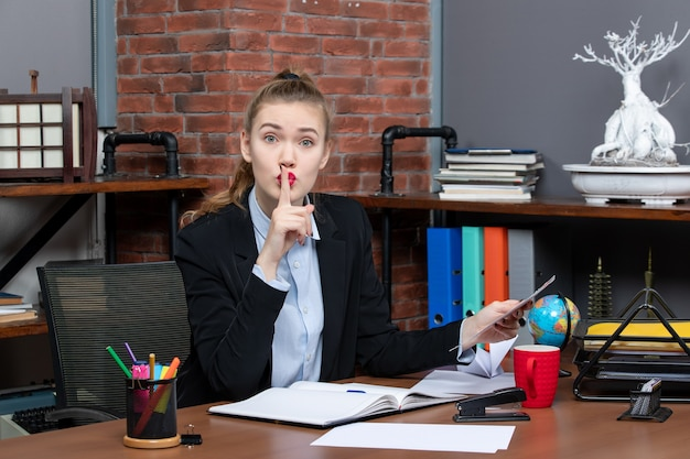 テーブルに座って、オフィスで沈黙のジェスチャーを作るドキュメントを保持している心配している女性の上面図