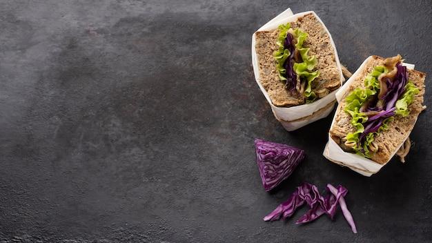 Вид сверху на завернутые бутерброды с салатом с копией пространства