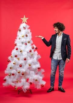 빨간색에 크리스마스 트리를 가리키는 수염 된 젊은 남자와 크리스마스 축하의 상위 뷰