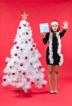 Вид сверху на рождественское настроение с красивой девушкой в черном платье с шляпой санта-клауса, стоящей возле елки