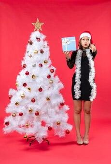 Вид сверху на рождественское настроение с красивой девушкой в черном платье с стоячей шляпой санта-клауса